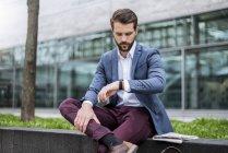Молодий бізнесмен сидячи на відкритому повітрі перевірка часу — стокове фото