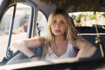 Ritratto di giovane donna seduta in macchina — Foto stock