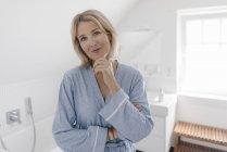 Porträt einer lächelnden reifen Frau im Badezimmer — Stockfoto