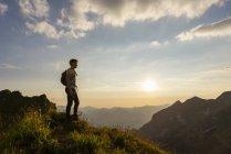 Homme debout dans la montagne colline au coucher du soleil — Photo de stock
