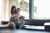 Щаслива пара на дивані вдома спільний доступ до планшета — стокове фото