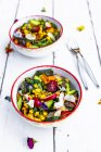 Bowls of mixed salad with edible flowers — Stock Photo