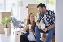 Man and pregnant woman moving into new flat having a coffee break — Stock Photo