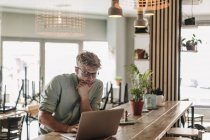Giovane uomo che lavora in startup cafè, utilizzando il computer portatile — Foto stock