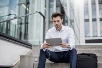 Businessman sitting on stairs with earbuds and tablet — Stock Photo