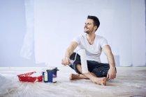 Hombre sonriente sentado en un apartamento nuevo tomando un descanso de la pintura - foto de stock
