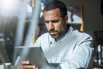 Человек за планшетом в кафе — стоковое фото