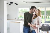 Man kissing pregnant woman in empty flat — Stock Photo