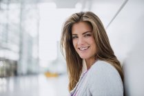 Porträt einer lächelnden jungen Frau, die sich an eine Wand lehnt — Stockfoto