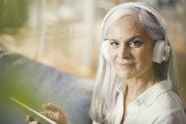 Старшая женщина с помощью цифровых планшетных компьютеров и наушников — стоковое фото