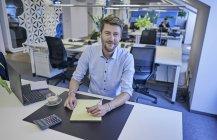 Porträt eines lächelnden Geschäftsmannes, der im Großraumbüro am Schreibtisch sitzt — Stockfoto