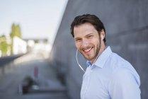 Retrato de homem de negócios sorrindo usando fones de ouvido — Fotografia de Stock