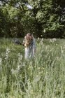 Italy, Veneto, Young woman plucking flowers and herbs in field — Stock Photo