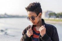 Retrato de mujer joven con gafas de sol de pie en el paseo marítimo - foto de stock
