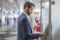 Young businessman withdrawing money at an ATM in the city — Stock Photo
