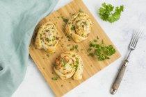 Petits pains collants avec feta, fromage à la crème, bacon et persil sur planche de bois — Photo de stock