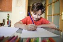 Portrait of smiling little girl drawing with coloured pencils at home — Stock Photo
