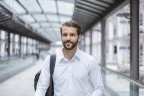 Портрет улыбающегося молодого бизнесмена на тротуаре — стоковое фото