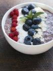 Ciotola di frullato di mirtilli con chia, fiocchi di cocco, mandorle e Wineberries giapponesi — Foto stock