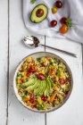Bol de salade de boulgour avec poivron, tomates, avocat, oignon de printemps et persil — Photo de stock