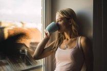 Café bebendo louro da mulher nova da caneca, olhando fora do indicador — Fotografia de Stock