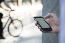 Рука бизнесмена с мобильным телефоном — стоковое фото
