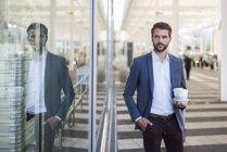 Jeune homme d'affaires tenant plateau avec café à emporter — Photo de stock