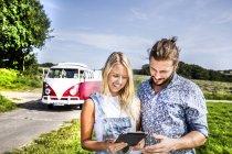 Coppia felice fuori van nel paesaggio rurale guardando tablet — Foto stock
