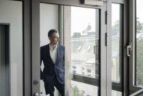 Бізнесмен в офісі дивиться з вікна — стокове фото