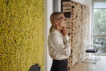 Businesswoman in office at wall with sunflowers thinking — Stock Photo