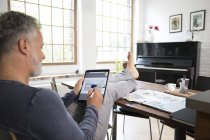 Mature man working from his home office with feet up, using tablet — Stock Photo