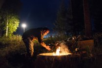 Finland, Man warming up at a camp fire on a camping ground — Stock Photo