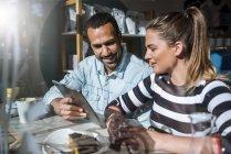 Молодая женщина и мужчина делятся планшетом в кафе — стоковое фото