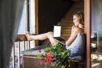 Женщина отдыхает на балконе с помощью ноутбука — стоковое фото