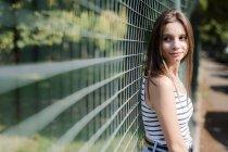 Retrato de una joven sonriente parada en una valla - foto de stock