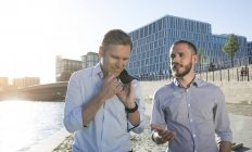 Two businessmen talking at riverbank in city — Foto stock