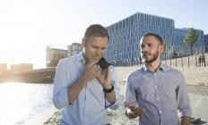 Due uomini d'affari che parlano alla riva del fiume in città — Foto stock