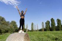 Jeune athlète restant sur la balle de paille, soulevant des bras sous le ciel bleu — Photo de stock