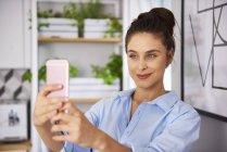 Jeune femme prenant selfie à la maison — Photo de stock