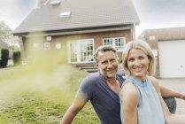 Портрет улыбающейся зрелой пары, сидящей в саду дома — стоковое фото