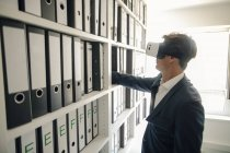 Empresário com óculos VR no arquivo da empresa, procurando prateleira com arquivos — Fotografia de Stock