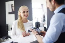 Mujer pagando en peluquería - foto de stock