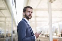 Young businessman holding cell phone looking sideways — Stock Photo