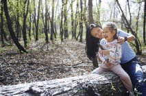 Mother and daughter in park, sitting on tree trunk — Stock Photo