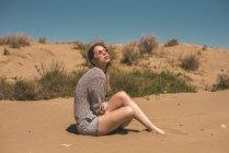 Spagna, giovane donna con gli occhiali da sole seduta sulla spiaggia rilassante — Foto stock