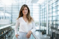 Portrait of smiling young woman standing at railing — Stock Photo