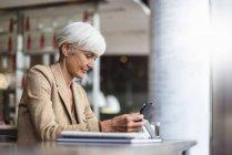 Старшая бизнес-леди, использующая планшет в кафе — стоковое фото