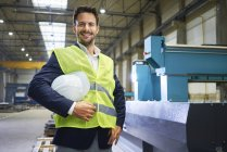 Portrait of smiling manager holding hard hat in factory — Stock Photo