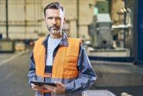 Портрет людини тримає таблетку в заводських умовах — стокове фото