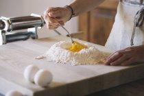 Женщина готовит тесто для макарон, муку и яйца — стоковое фото